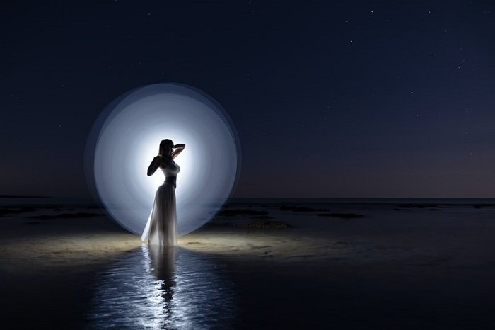 Night light painting with a white light imitating the moon behind a woman
