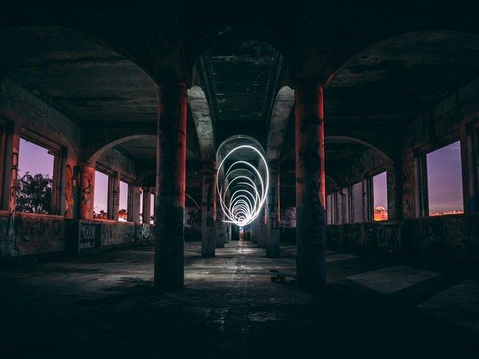 spiral light painting at golden hour under a concrete bridge