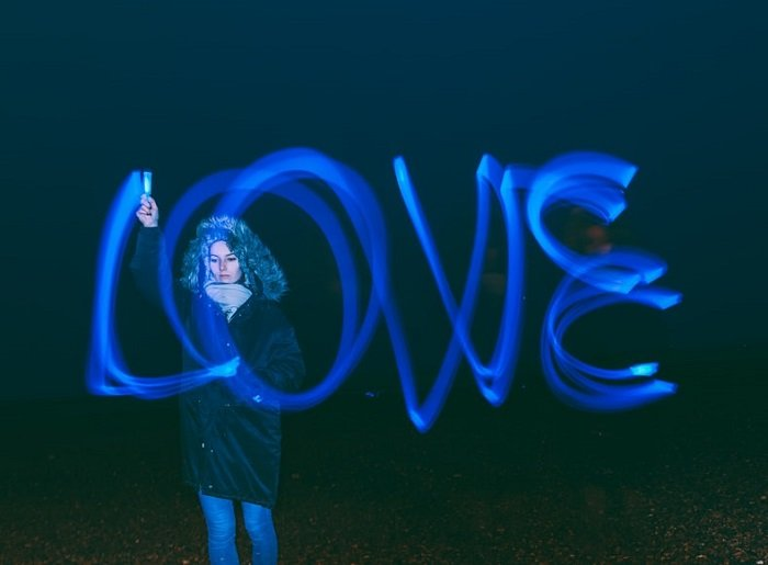 """woman using a night light painting photography technique to spell """"LOVE"""""""