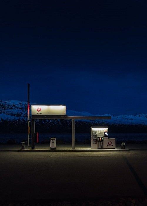 在昏暗的光线下拍摄的汽油泵的图像,背景是黑暗的风景