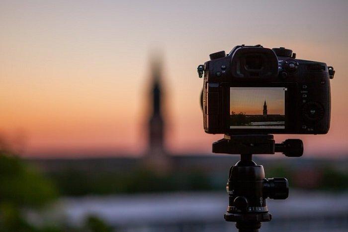 三脚架上相机的图像,背景为模糊的日落