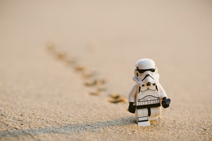 miniature photography of a stormtrooper trekking through sand