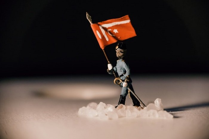 miniature photography of a soldier carrying a flag through snow