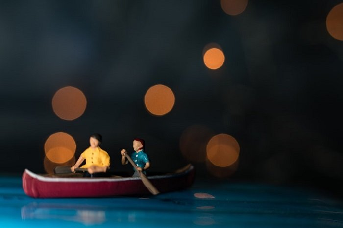miniature photography of two people in a canoe