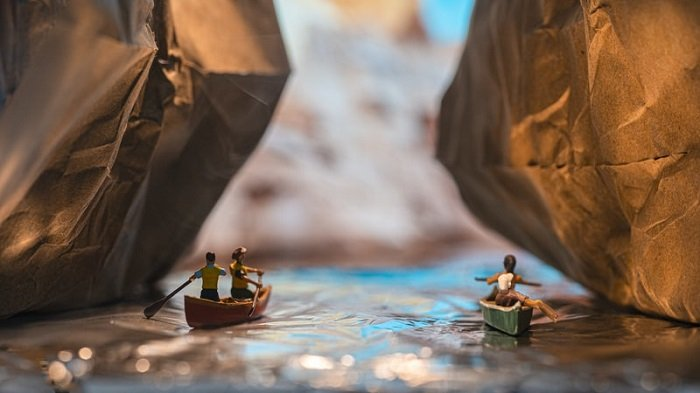 miniature photography of two couples in canoes
