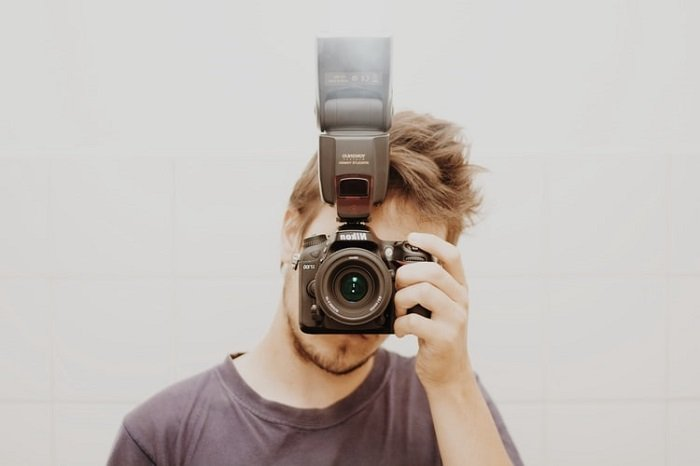 man holding a camera with an off-camera flash