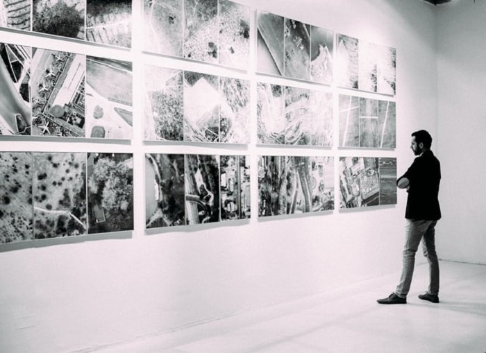 black and white image of a man viewing images in a gallery