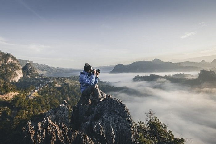 photographer sitting on a cliff with a mountain landscape in the background