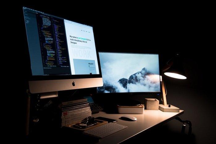 imac on a desk beside a lamp