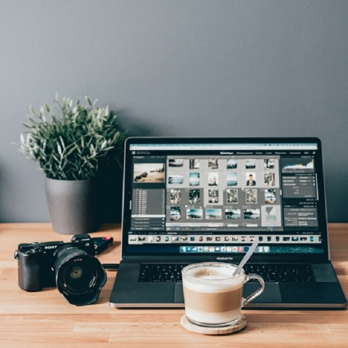 cup of coffee and camera beside a macbook pro with photos opened