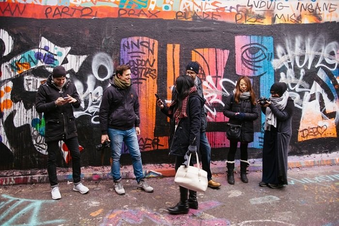 6 photographers talking against a colorful wall