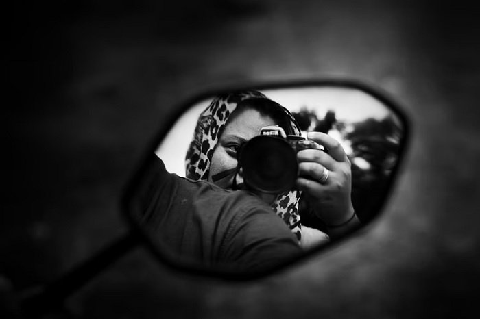a black and white self portrait reflection taken in a car side mirror