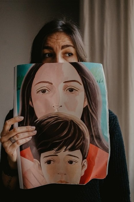 a self portrait of a woman holding a picture of another woman and young boy