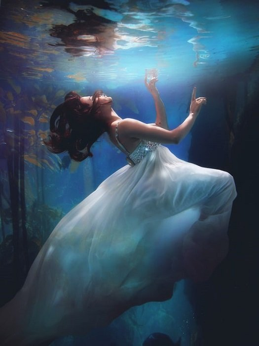 woman in a white dress floating underwater