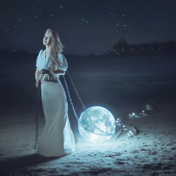 image of a woman dragging the moon behind her using a chain with cool blue tones