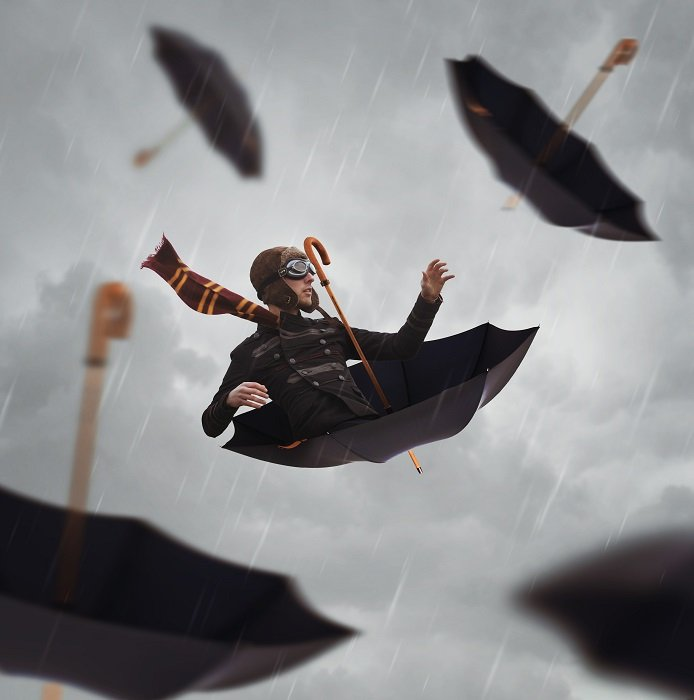 man nestled in an upside down umbrella floating in a grey sky