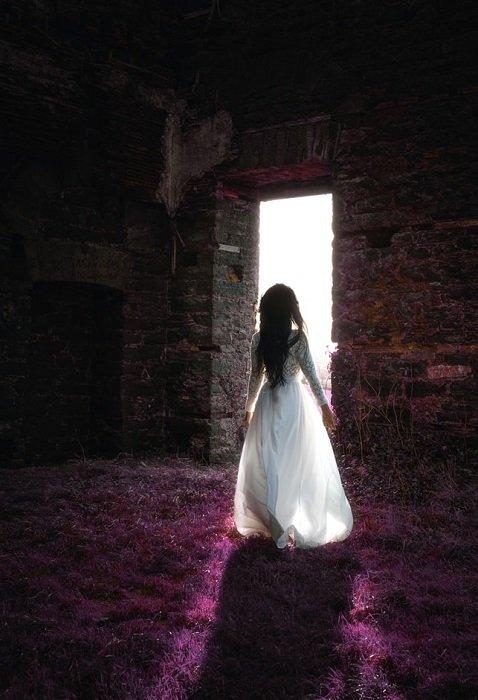 girl walking towards a bright stone door