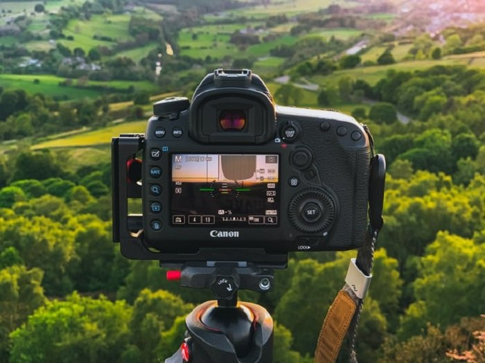 camera set up on a tripod looking out at a countryside landscape