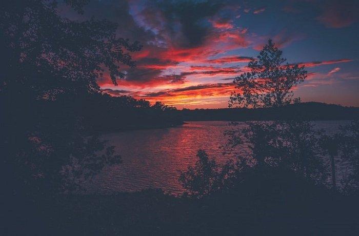 bright orange and red clouds over a dark sunset scene