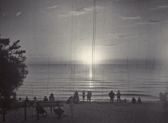 black and white film photograph of a seafront sunset