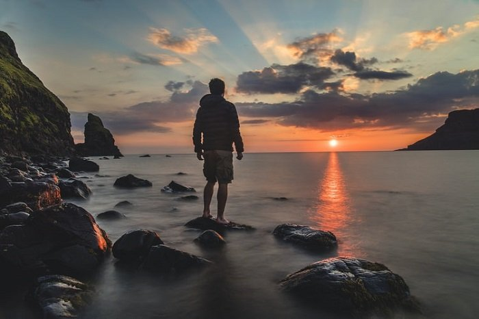 man standing at a seashore with a sunset in the background