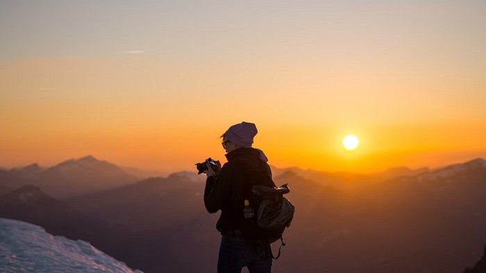 Photographer in a mountainous scene with a sunset in the background