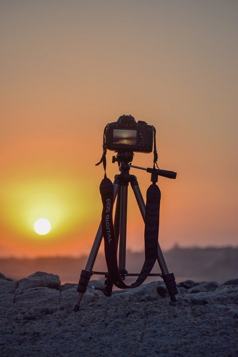 camera on a tripod aimed at a sunset