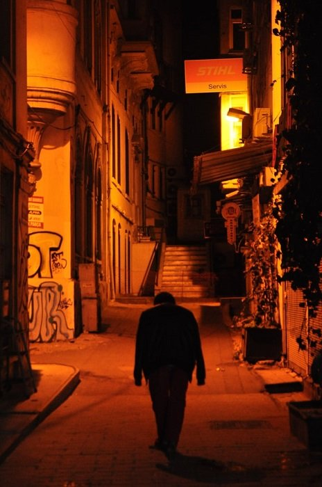 A raw style street photograph of a dark silhouette in an empty alleyway with their down with red and orange lighting