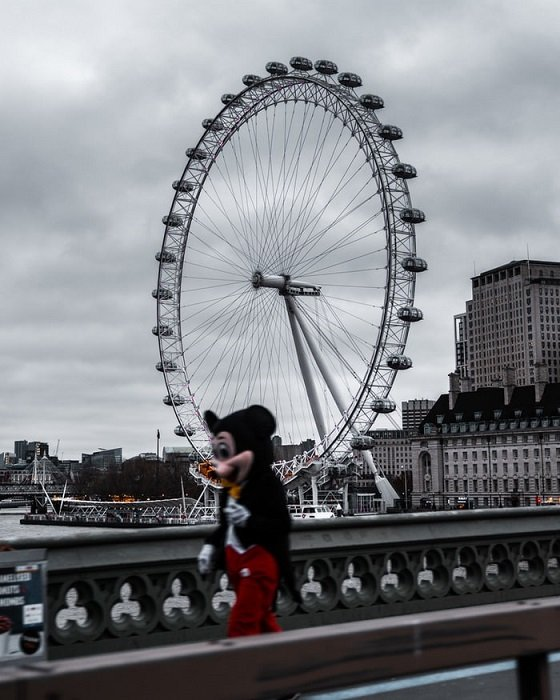 A photo of the London Eye in the background with a blurred person in a Mickey Mouse costume walking by in the foreground