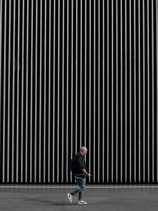 A man walking by a large wall with thin graphic white lines on a black background