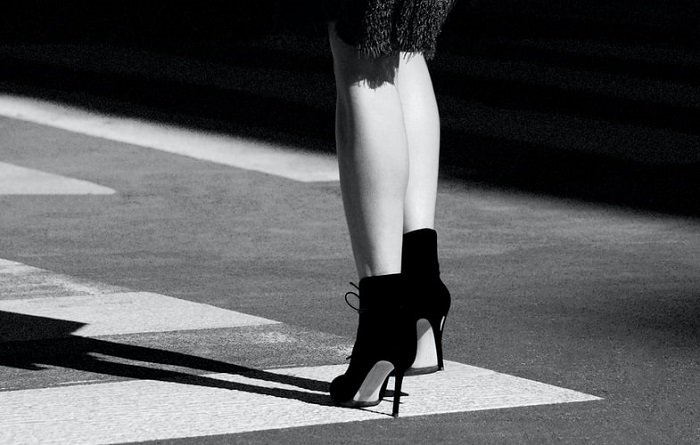 A black-and-white abstract photo of a woman's lower legs and feet in high heels on a street sidewalk