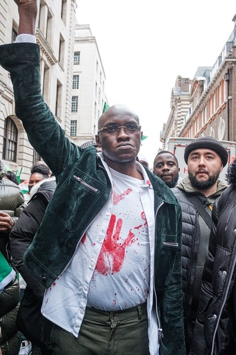 A Black man with his arm lifted in the air as a sign of protest waling with a group of people in the street