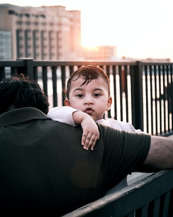 A street portrait of a child looking over the shoulder of a man