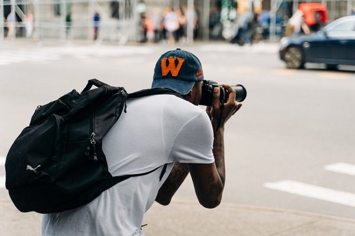 Man bent over and looking trough a camera taking a photo in the street.