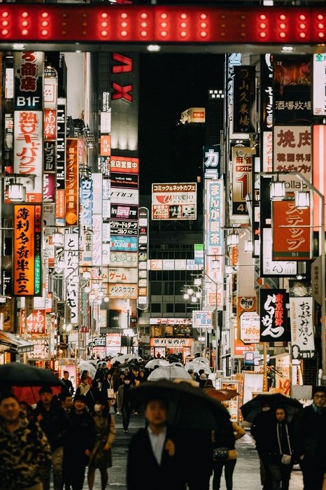 People with umbrellas walking down a pedestrian street in Japan filled with store signs at night