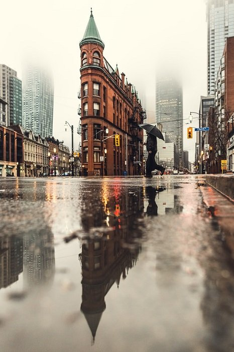 A low-perspective shot of a building and its reflection in puddles on a rainy street scene