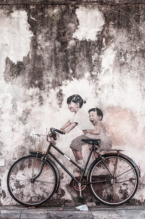 A black-and-white fine-art street photograph of two children sitting on a bike against a wall and laughing