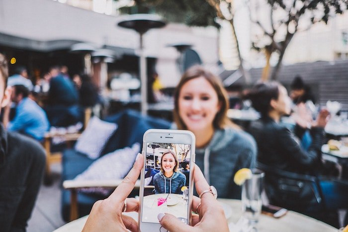 woman in an outdoor restaurant being photographed by a smartphone
