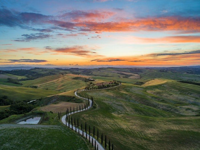 Tuscany sunset landscape image of a winding road and green hills
