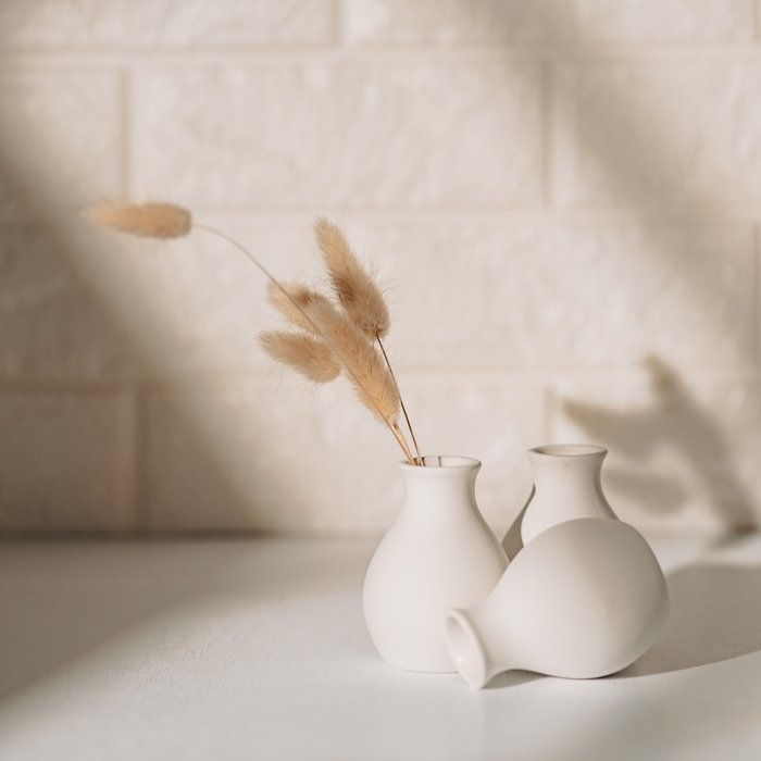 Lifestyle photo of small, white vases with wheat
