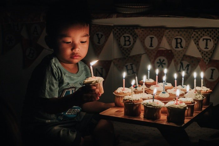 Child holding cupcake with lit candle and tray of cupcakes with lit candles