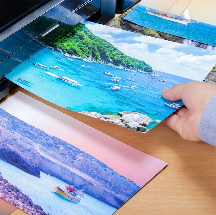 Photographer pulls out enlarged photo printed on a photo printer
