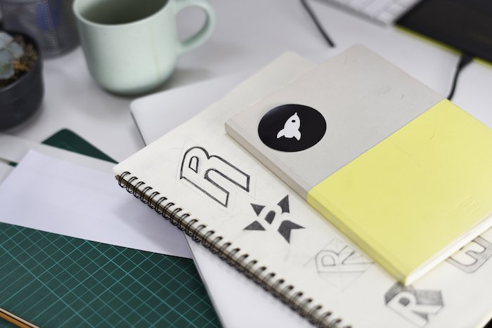 A notebook with brand logo ideas