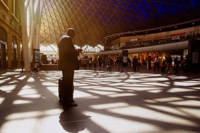 A man at a train station surrounded by shadows with ON1 edit