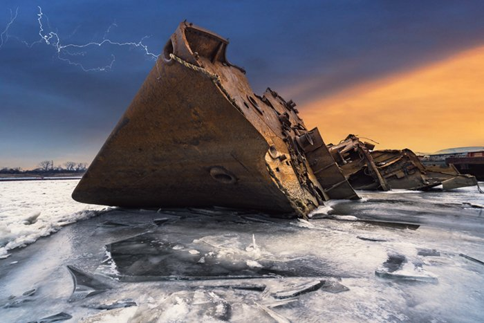 Rusted shipwreck on icy water with lightning in the sky