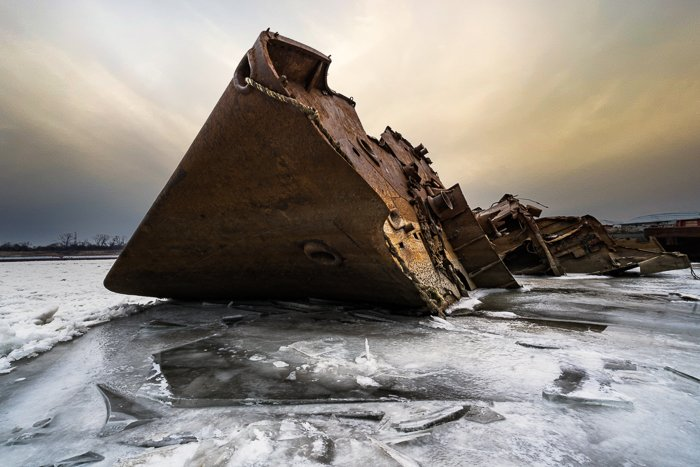 Rusted shipwreck on icy water with AI sky replaced using Adobe Photoshop