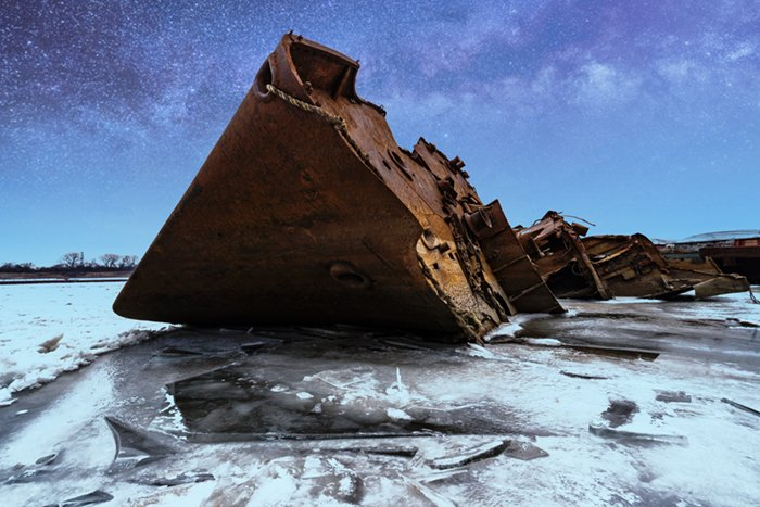 Rusted shipwreck on icy water with a starry sky added using Picnic