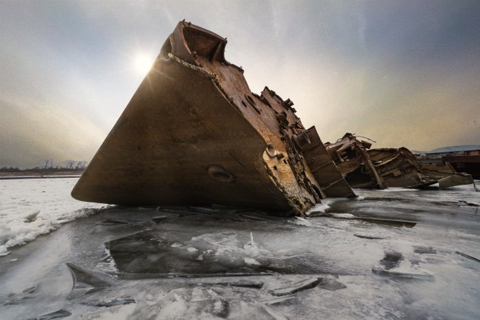Rusted shipwreck on icy water with sunny AI sky replacement using Luminar AI