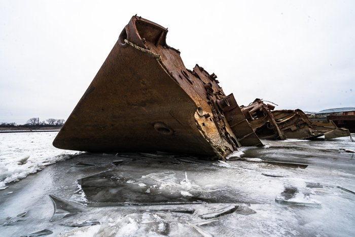 Rusted shipwreck on icy water with cloudy washed out sky