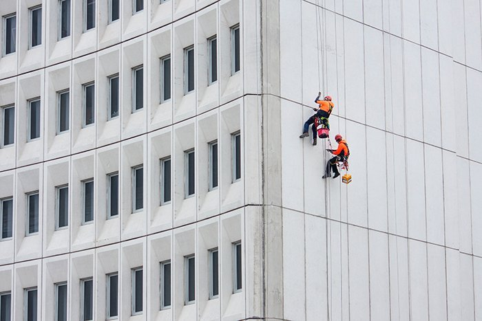 color in photography: two workers dressed in bright orange suspended from the side of a building